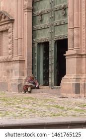 Cusco, Peru 12/17/17- Cusco Cathedral entrance in plaza de armas Peru with man sitting on steps.