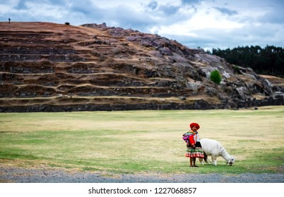 Cusco, Peru - 13 October 2018: View of woman in national clothing shepherd white lama on the background of rocky hill in Sacsayhuaman