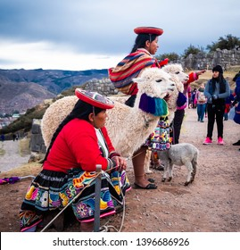 Cusco, Peru - 13 October 2018: women in colorful national clothing with lamas in fancy decorations on the background of Sacsayhuaman landscape with tourists
