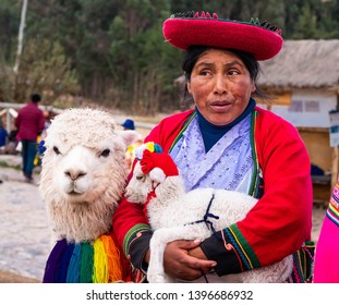 Cusco, Peru - 13 October 2018: View of woman in colorful national clothing holding little white lama in Sacsayhuaman
