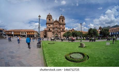 Cusco, Peru - Apr 6, 2017: Plaza de Armas city architecture, stone buildings walls, cobblestone street. Wide angle panoramic photo. Sunny day, Blue sky.