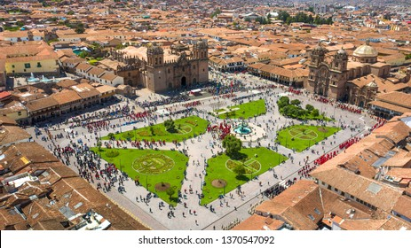 """Cusco, Peru - April 14 2019: Aerial view of the Cusco's main plaza with crowd of people watching the flag raising act. Touristic plaza named """"Plaza de Armas"""" in the colonial historic center."""