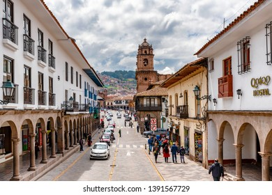 Cusco, Peru - April 3, 2019: View at the traffic on the street with old colonial buildings and Plaza de Armas with a church at the background in Cusco, Peru.