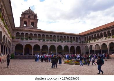 CUSCO / PERU, August 14, 2018: Tourists explore the courtyard of Qorikancha in Cusco.