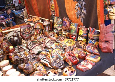 CUSCO, PERU - AUGUST 24 : Young woman sells painted Inca masks at Pisac Sunday Market on August 24, 2008 in Cusco, Peru.