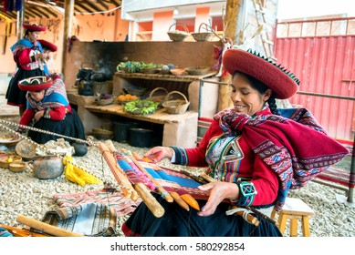 CUSCO, PERU - FEB 11: A Quechuan woman demsontrates alpaca wool weaving on February 11, 2017. The  many colors are provided by vegetable dyes from different plants.