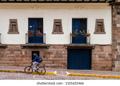 Cusco, Peru - February 10, 2018: Man makes an effort to climb with his bicycle on a typical street of the San Blas neighborhood, in the city of Cusco