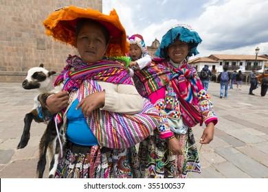 CUSCO, PERU, JANUARY 14: Peruvian Indian women in traditional clothes carrying babies and a baby sheep on the Plaza de Armas of Cusco. Peru 2015