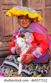 CUSCO, PERU - JANUARY 20: Unidentified woman in traditional dress holds lamb in the street on January 20, 2015  in Cusco, Peru. In 1983 Cusco was declared a World Heritage Site by UNESCO.
