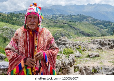 Cusco, Peru; January 24, 2017: Old man Quechua dressed in a colored poncho and a cap of Chullo, plays on the musical instrument quena with a view of the mountains in the background
