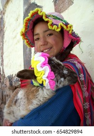Cusco, Peru - January 7, 2007: Unidentified Quechua girl in traditional colorful clothing with a baby sheep.
