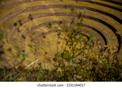 Cusco, Peru - July 12, 2018: Inca depressions formed by perfect agricultural circles in the Sacred Valley. One of the main tourist destinations of Cusco in Moray. Inca ruins, archaeological site.