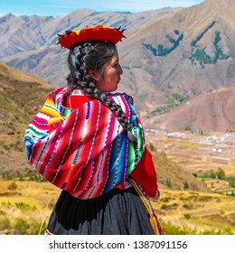 CUSCO, PERU - JULY 18, 2018: A Quechua indigenous woman looking over the Sacred Valley of the Inca in the archaeological site of Tipon in the Andes mountain range near Cusco, Peru.