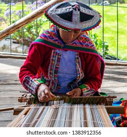 CUSCO, PERU - JULY 19, 2018: Square photograph of a Quechua indigenous woman showing the traditional weaving technique and the manufacturing of textiles in the Andes mountain range of South America.