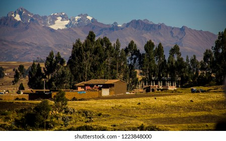 Cusco, Peru - July 2, 2018: Houses of the city of Racchi surrounded by trees of the plateau of Chinchero and as background the majestic Andes Mountain Range. Landscapes to enjoy.