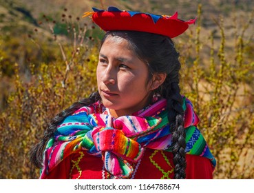 CUSCO, PERU - JULY 24, 2018: Portrait of an indigenous Peruvian Quechua woman with traditional colorful clothing in the Andes mountain range near the archaeological site of Tipon near Cusco city.