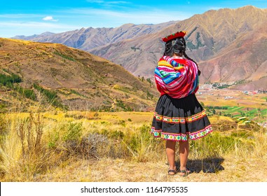 CUSCO, PERU - JULY 24, 2018: An indigenous Peruvian Quechua lady looking at the Andes Mountain Range in the Inca ruin of Tipon in the region of Cusco, Peru. Square format.