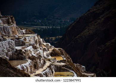 Cusco, Peru - July 7, 2018: pre-Inca salt ponds traditional salt in Maras located in the Urubamba, as background the trees of the Andes. The Salar de Maras is one of the main tourist attractions.