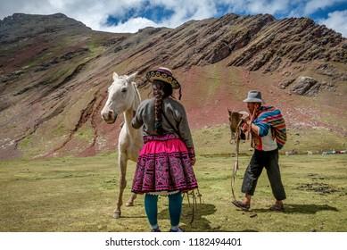 Cusco, Peru- March 18, 2017:Woman with a horse on Vinicunca aka Rainbow Mountain in the region of Cusco, Peru