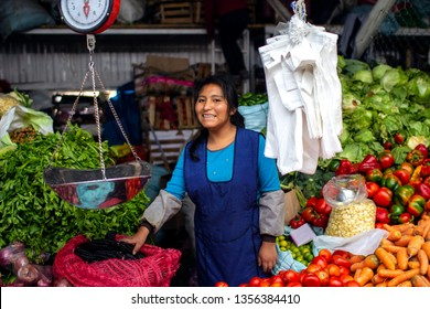"""Cusco, Peru - March 31 2019: Indigenous young woman smiling and selling vegetables at """"Vinocanchon San Jeronimo"""" market. Happy Peruvian female shopkeeper at food stand."""