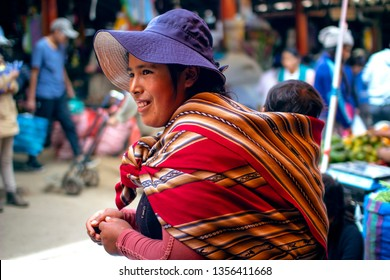 Cusco, Peru - March 31 2019: Peruvian indigenous mother carries her baby son on her back with traditional inca fabric. Native poor female smiling at local market.