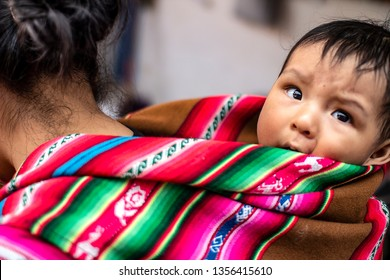 Cusco, Peru - March 31 2019: Peruvian indigenous mother carries her baby son on her back with traditional inca fabric. Native poor baby at local market.