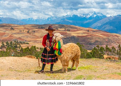 CUSCO, PERU - OCTOBER 1, 2018: An indigenous Quechua lady with alpaca in front of a beautiful landscape in the Andes mountain range of the Sacred Valley of the Inca near Cusco.