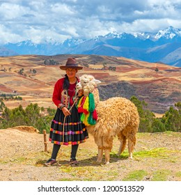 CUSCO, PERU - OCTOBER 2, 2018: Indigenous Quechua lady in traditional clothing (dress, textile, hat) with her alpaca in the Sacred Valley of the Inca and the Andes mountain range in the background.