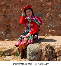 CUSCO, PERU - SEPTEMBER 11, 2018: A young indigenous Quechua woman sitting on an ancient Inca Wall, Cusco, Peru.