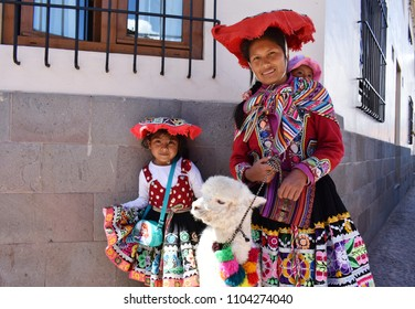 Cusco, Peru, South America- May 2018. Peruvian mother and her children, in traditional dress, pose with their alpaca.