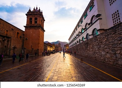 Cusco street with beautiful ancient architecture and people walking along