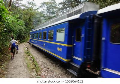 Cusco/Peru - Oct.06.19: touristic train to Aguas Calientes and trekker besides it. Way to Machu Picchu.