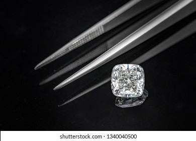 Cushion cut diamond with tweezers on black reflection background
