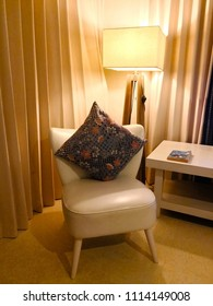 Cushion with floral pattern, which uses local woven fabric. Place on the white chair. At the corner of the room  near the table with the book. And the back is cream curtain with a lamp made of wood.
