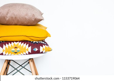 Cushions on the chair white wooden background with copy space. Sweet home and cozy concept. Close up