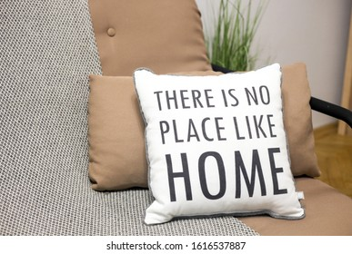 Cushions on a sofa with a text There is no place like home, living room interior design details, cozy house