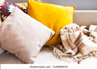 Cushions and plaid on the beige sofa close up with copy space. Sweet home and cozy concept. Indoors