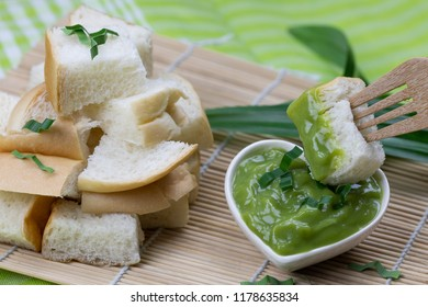 Custard bread in wooden tray and pandan paste on green cloth floor with copy space Thai dessert