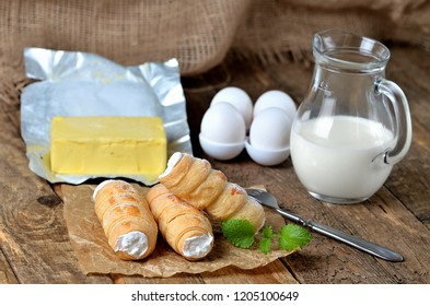 Custard tube of pastry filled with cream traditional czech sweet, butter, eggs, mint leaves and milk on wooden table