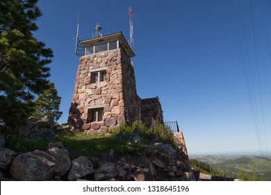 CUSTER STATE PARK, SOUTH DAKOTA - June 9, 2014:  Mount Coolidge Fire Lookout building with antennas and wires against a clear blue sky in Custer State Park, SD on June 9, 2014.