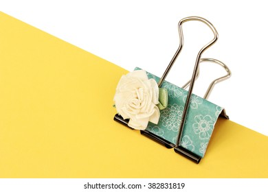 A custom binder clip attached to yellow paper with clipping path over white