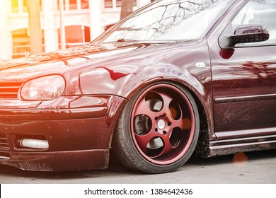 Custom brown forged wheels on a low tuned stance car who stays on a street. dirty Lowrider on a air suspension at sunny day.