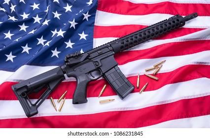 Custom built AR-15 carbine and bullets on American flag surface, background. Studio shot.