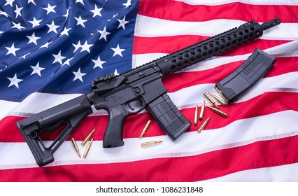 Custom built AR-15 carbine, bullets and a magazine on American flag surface, background. Studio shot.