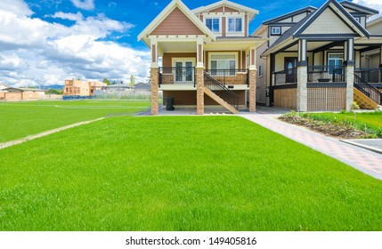 Custom built big luxury house with nicely trimmed front yard, lawn and a soccer field aside in a residential neighborhood. Vancouver Canada.