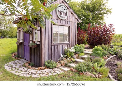 A custom built cottage like garden shed with a cobblestone sidewalk, purple door, window flower boxes, and wood board and batten siding.