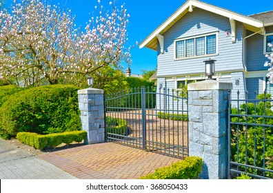 Custom built house behind the gates and with nicely trimmed and landscaped front yard, lawn in a residential neighborhood. Vancouver Canada.