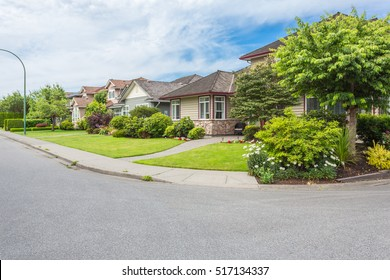 Custom built luxury homes with nicely trimmed and designed front yard, lawn in a residential neighbourhood in Canada. Street of houses.