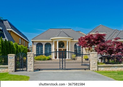 Custom built luxury house behind the metal gates and with nicely trimmed and landscaped front yard, lawn in a residential neighborhood. Vancouver Canada.
