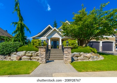 Custom built luxury house with nicely paved and stoned doorway and trimmed front yard, lawn in a residential neighborhood. Vancouver Canada.